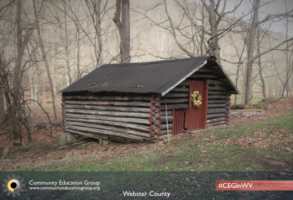 A log cabin with a red door and a golden wreath in Webster County, West Virginia